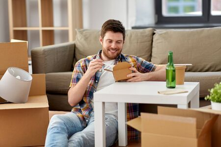 moving, consumption and people concept - smiling man eating takeaway food for lunch at new home Stockfoto