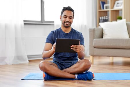 sport, technology and healthy lifestyle concept - smiling indian man with tablet computer sitting on exercise mat at home