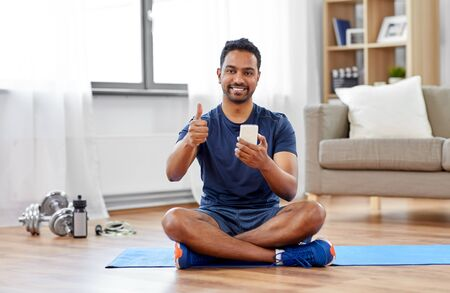 sport, technology and healthy lifestyle concept - smiling indian man with smartphone sitting on exercise mat and showing thumbs up at home