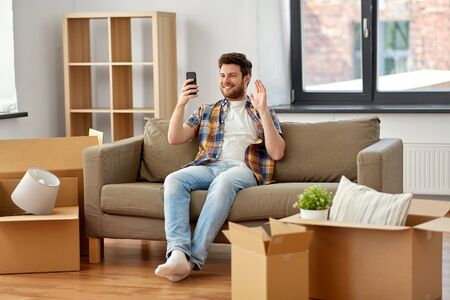 moving, people and real estate concept - happy man with smartphone and boxes sitting on sofa and having video call at new home