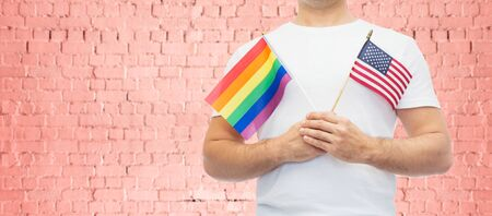 lgbt, same-sex relationships and homosexual concept - close up of man wearing gay pride rainbow awareness wristband and holding american flag over pink brick wall background