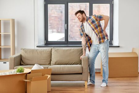 moving, people and real estate concept - man with sofa at new home suffering from back ache