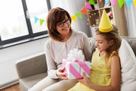 family, greetings and celebration concept - happy grandmother giving her granddaughter birthday gift at home
