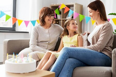 family, generation and celebration concept - smiling mother, daughter and grandmother at birthday party Stockfoto