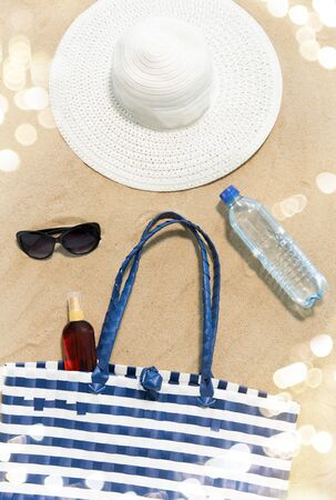beach bag, sunscreen, sunglasses and hat on sand