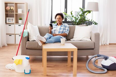 woman with smartphone resting after home cleaning Stockfoto