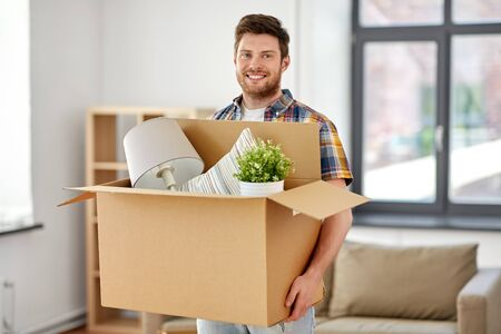 moving, people and real estate concept - happy man with boxes at new home