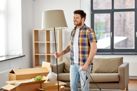 moving, people and real estate concept - happy man with floor lamp at new home
