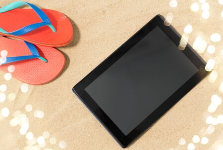technology, vacation and summer holidays concept - tablet computer and flip flops on beach sand