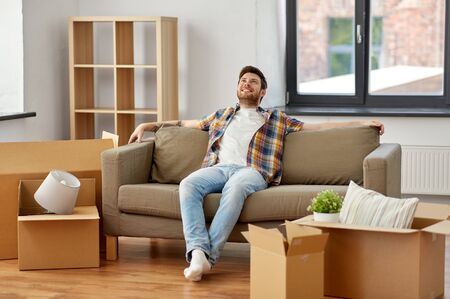 moving, people and real estate concept - happy man with boxes sitting on sofa at new home Stockfoto