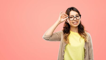 people, education and school concept - happy asian woman or student in glasses fixed by tape over living coral background