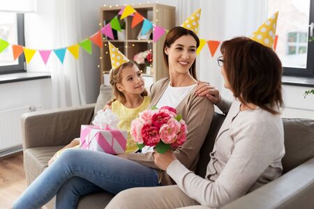 family, generation and celebration concept - smiling grandmother with flowers and daughter with gift box greeting mother on birthday at home