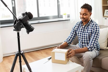 male video blogger opening parcel box at home Stockfoto