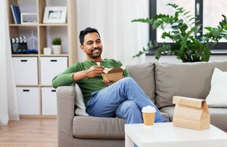 smiling indian man eating takeaway food at home Stockfoto