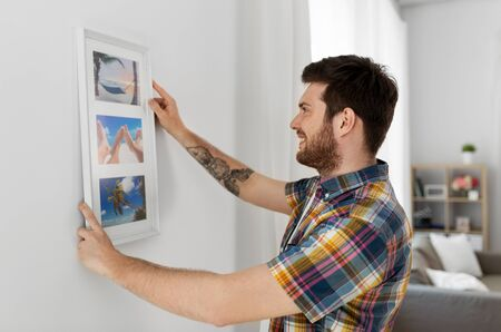 man hanging picture in frame to wall at home