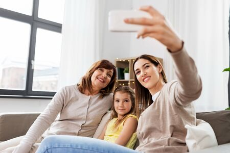mother, daughter and grandmother taking selfie