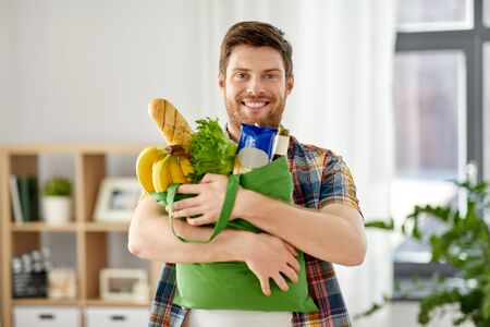 smiling young man with food in bag at home Stockfoto