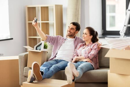 Couple taking selfie by smartphone at new home