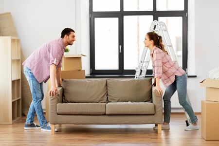 Happy couple moving sofa at new home Stockfoto