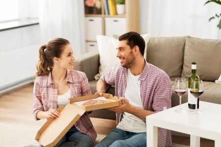 Couple with wine eating takeaway pizza at home Stock Photo - 124940229