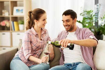 happy couple drinking red wine at home