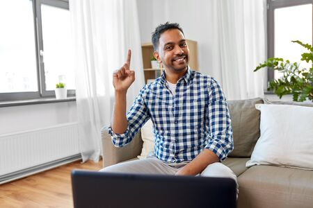 indian male blogger pointing finger up at home