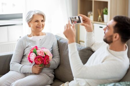 adult son photographing senior mother at home