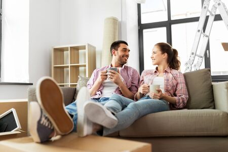 happy couple drinking coffee moving to new home Stock Photo