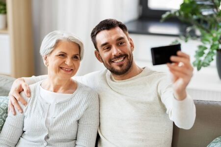 Senior mother with adult son taking selfie at home Stockfoto