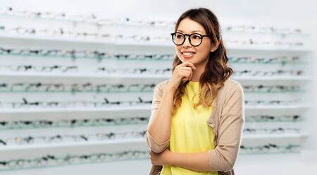 Happy Asian woman in glasses over optics store