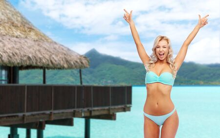 Happy young woman in bikini doing fist pump
