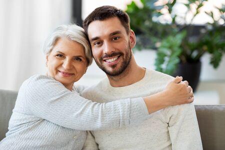 Senior moeder met volwassen zoon knuffelen thuis Stockfoto