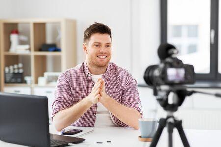 male blogger with camera videoblogging at home Banco de Imagens