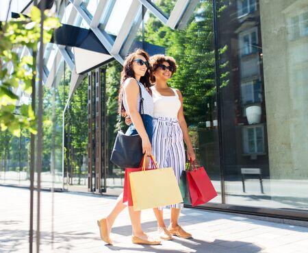 women with shopping bags on city street in summer