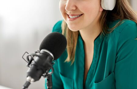 woman with microphone recording podcast at studio Banco de Imagens