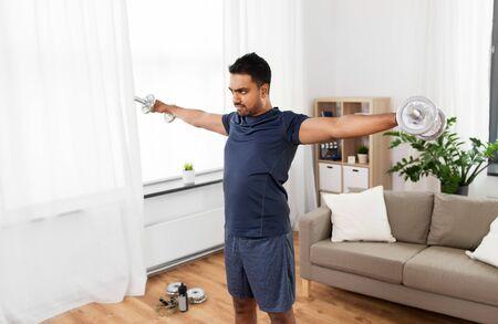 indischer Mann, der zu Hause mit Hanteln trainiert Standard-Bild