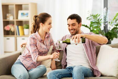 couple heureux buvant du vin rouge à la maison Banque d'images