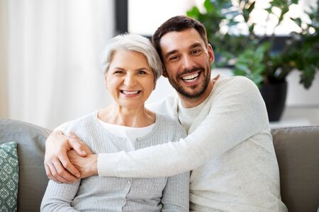 senior mother with adult son hugging at home