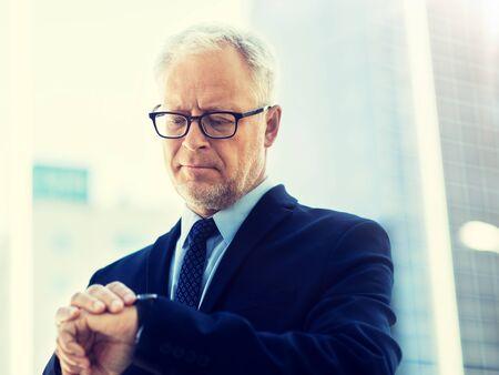 Senior businessman checking time on his wristwatch