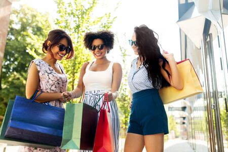 Happy women showing shopping bags in city Stock Photo
