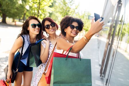 Women with shopping bags taking selfie in city Stock Photo