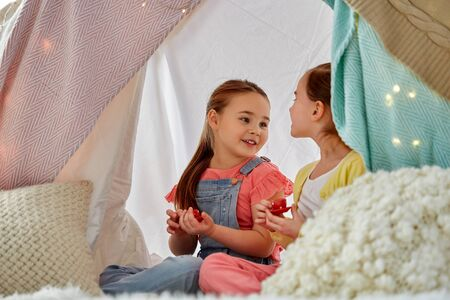 Little girl playing tea party in kids tent at home Фото со стока
