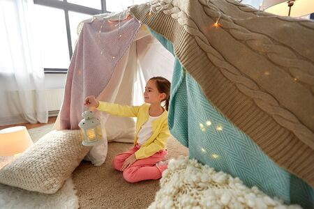 Little girl with lantern in kids tent at home