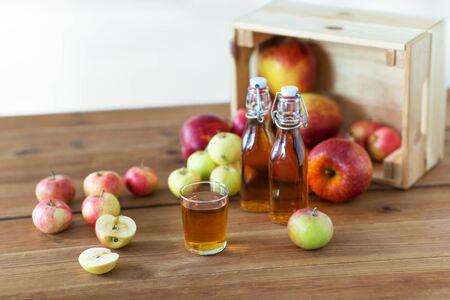 Verre et bouteilles de jus de pomme sur table en bois Banque d'images