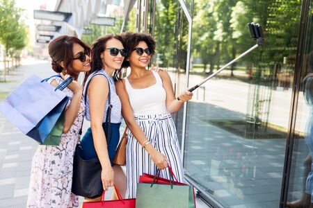 Women with shopping bags taking selfie outdoors
