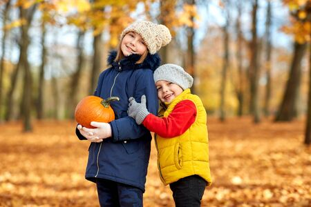 Happy children with pumpkin hugging at autumn park