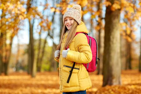 Happy student girl with schoolbag at autumn park