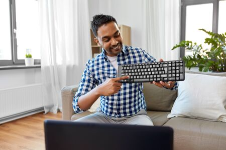 Male blogger with keyboard video blogging at home Banco de Imagens