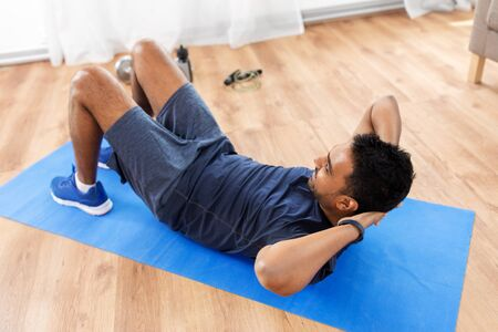 Indian man making abdominal exercises at home Stockfoto