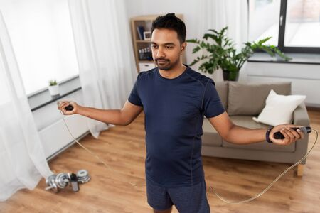 Indian man exercising with jump rope at home